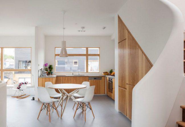 Белая кухня в сочетании с деревянной мебелью цвета ясеня выглядит тепло и уютно