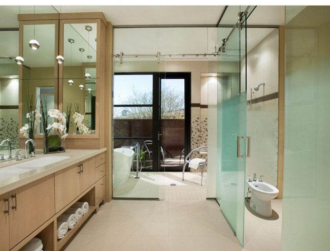 Тумбочки из светлого ясеня, зеркала, прозрачные перегородки добавляют «воздушности» и «легкости» ванной комнате