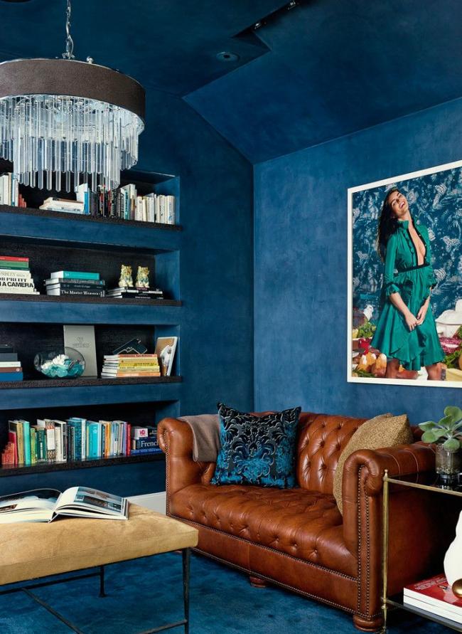 Красивый синий интерьер в стиле фьюжн с небольшим диваном Честерфильд коричневого цвета