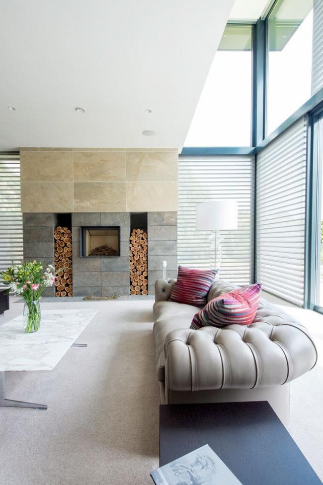 Просторный интерьер гостиной частного дома с серым диваном Честерфилд в современном оформлении