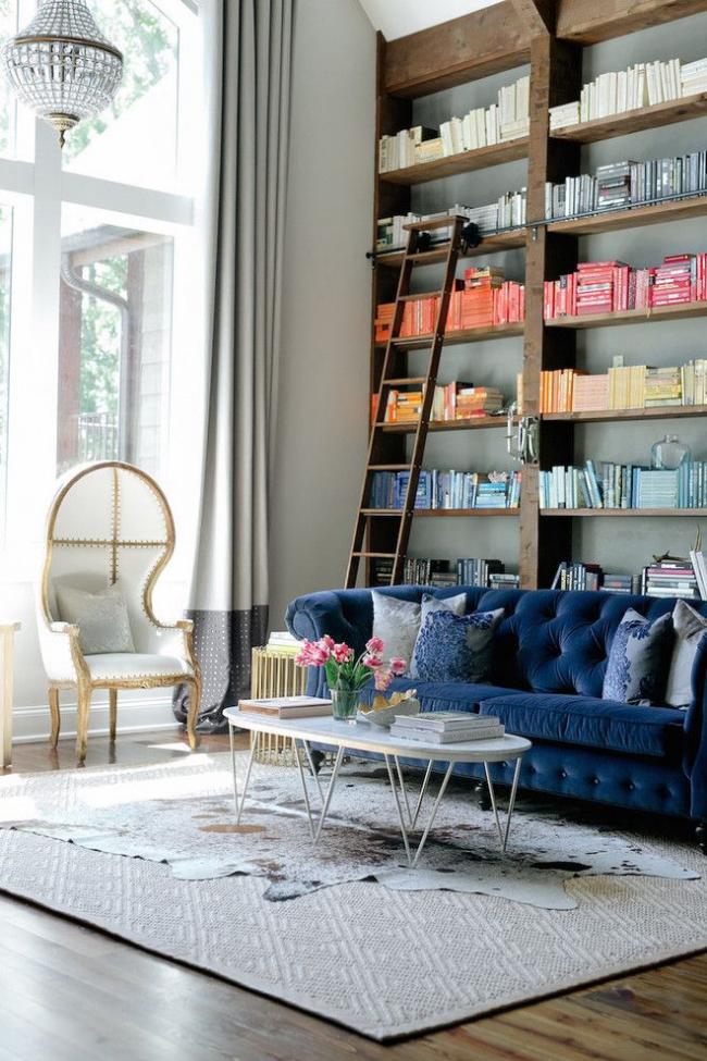 Небольшой синий диван на маленьких ножках в интерьере серых тонов