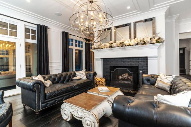 Классические кожаные диваны Честерфильд черного цвета в черно-белой гостиной
