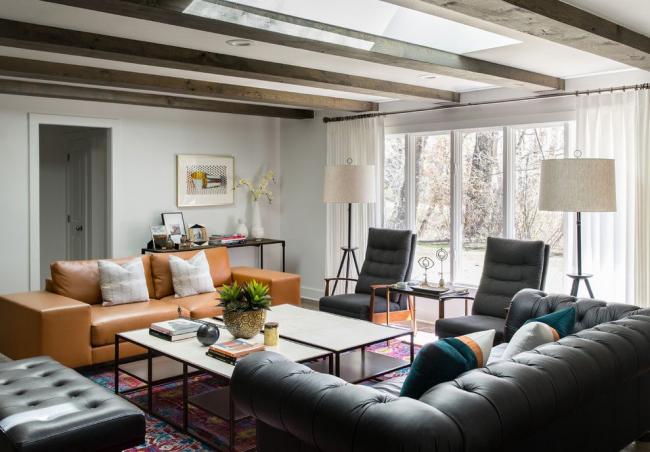 Квадратная светлая гостиная с темным диваном Честерфилд