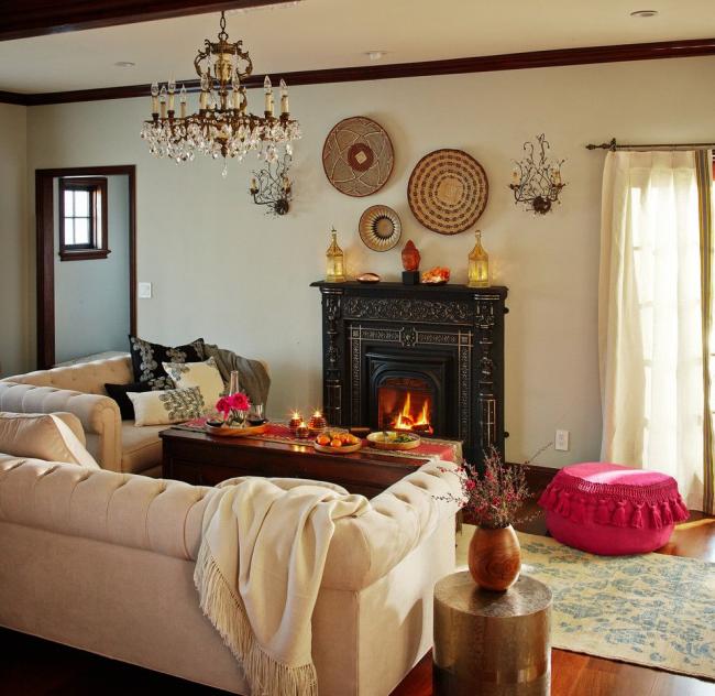 Светлый диван Честерфилд в гостиной с камином