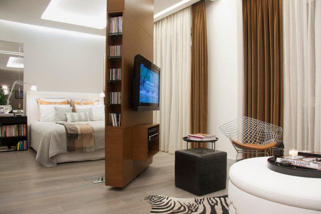 Поворотная перегородка с телевизором в интерьере спальни-гостиной