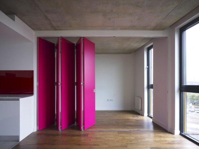 Эффектная складная дверь розового цвета станет ярким элементом декора в интерьере кухни