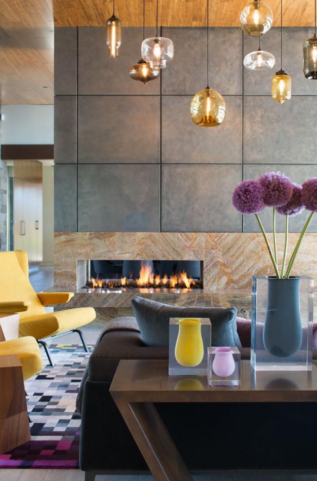 Камин является дизайнерским решением, который позволяет избежать однообразия и помогает сделать комнату уютной и привлекательной