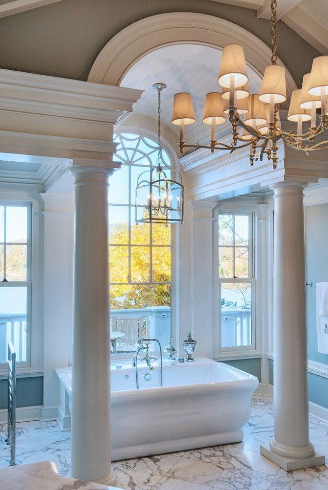 Необычная ванная комната с большими окнами, колонами и пилястрами