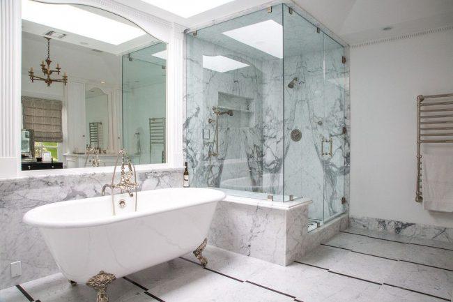 Красивая светлая ванная комната с мраморной отделкой и белыми пилястрами