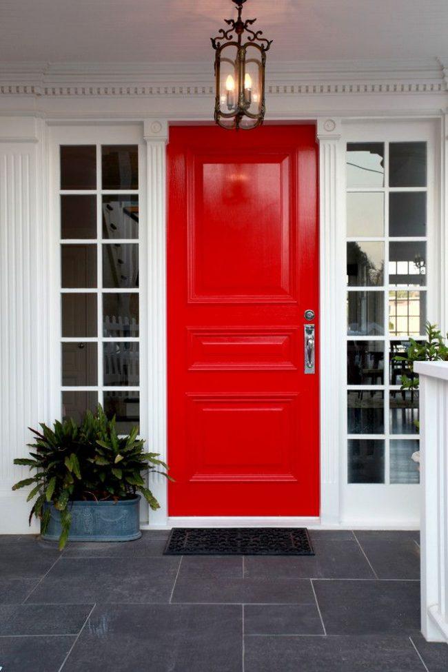 Красивое контрастное сочетание входной двери красного цвета и аккуратных белых пилястр