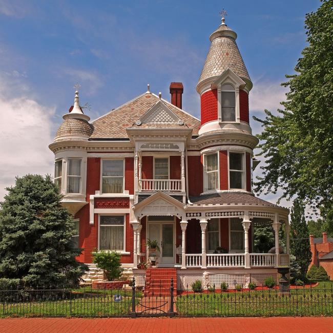 Яркий красно-белый дом с маленькой круглой жилой башенкой