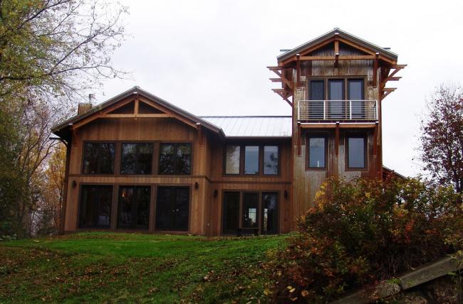 Современный загородный деревянный дом с большими окнами и башней