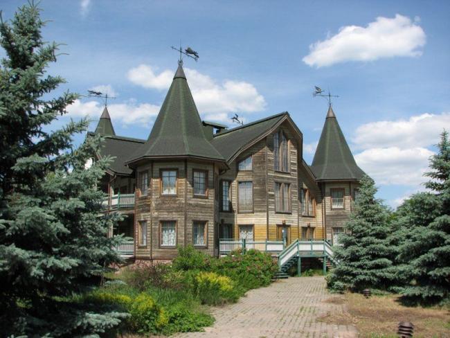 Деревянный дом с башнями и флюгерами