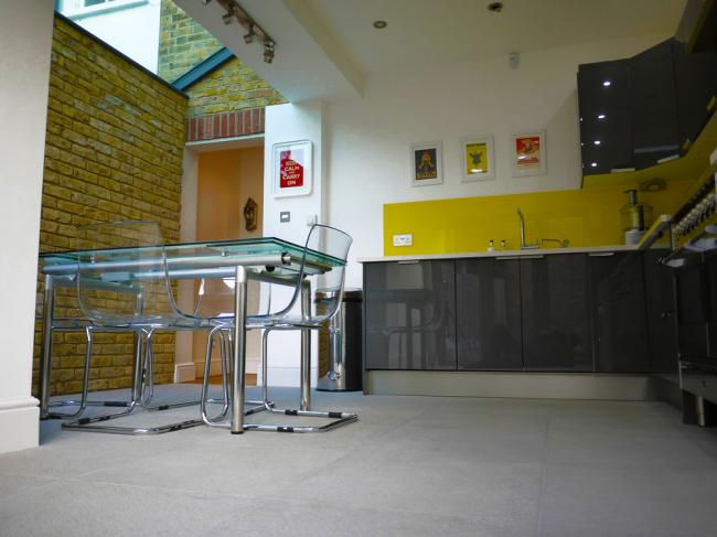 Стеклянный раздвижной стол на современной кухне с кирпичной стеной