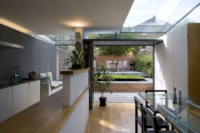 Большой стеклянный стол на современной минималистичной кухне