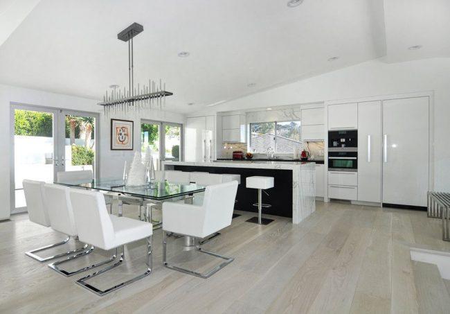 Просторная белая кухня с раздвижным стеклянным столом