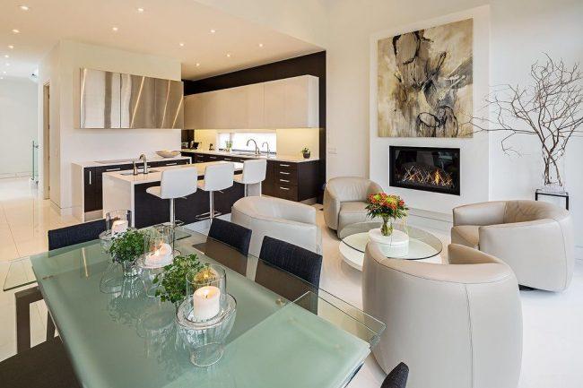 Современный интерьер кухни-студии с раздвижным стеклянным столом