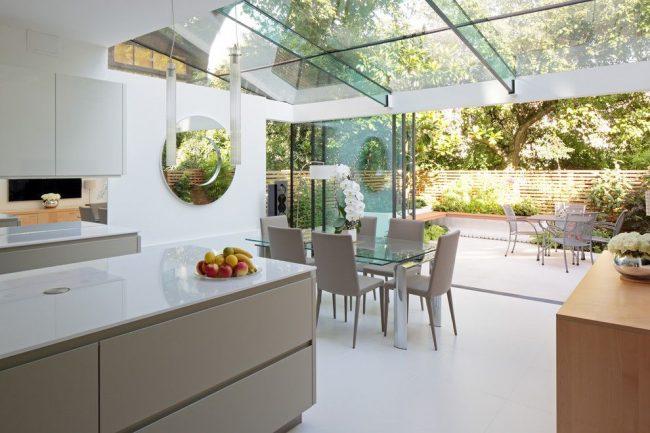 Светлый интерьер кухни в частном доме с раздвижным стеклянным столом