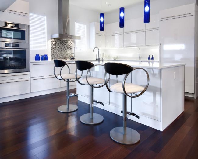 Современный проект белой кухни с барными стульями у острова