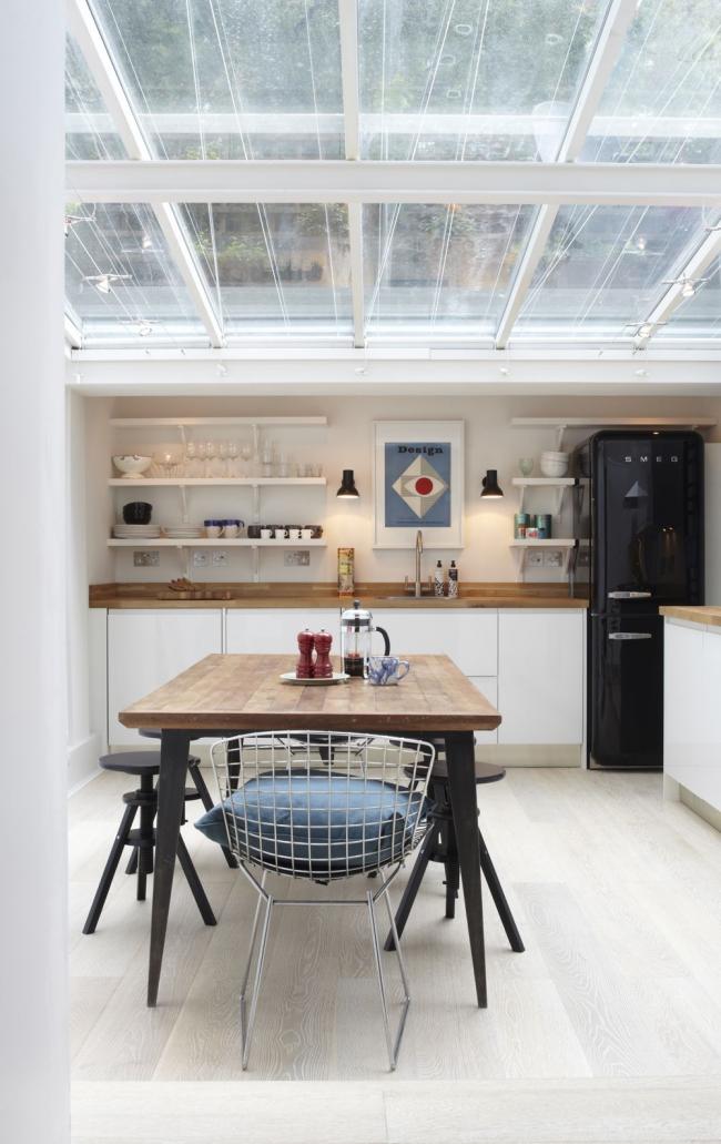 Элегантный черный холодильник на светлой просторной кухне