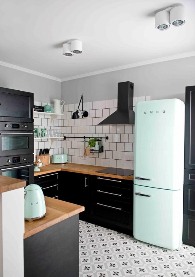 Большой фирменный холодильник марки Smeg на кухне в черно-белых мотивах с элементами гарнитура из натурального дерева