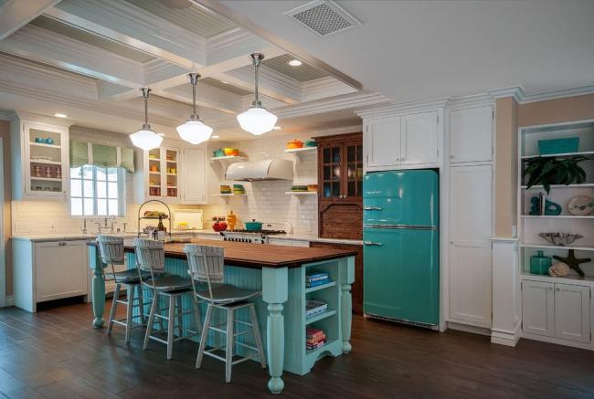 Просторная кухня-студия в светлых тонах с яркими акцентами на бирюзовом холодильнике и обеденной зоне в том же цвете