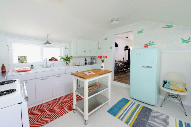 Нежный холодильник светлого голубого оттенка на небольшой кухне, зонированой с помощью цветовых акцентов