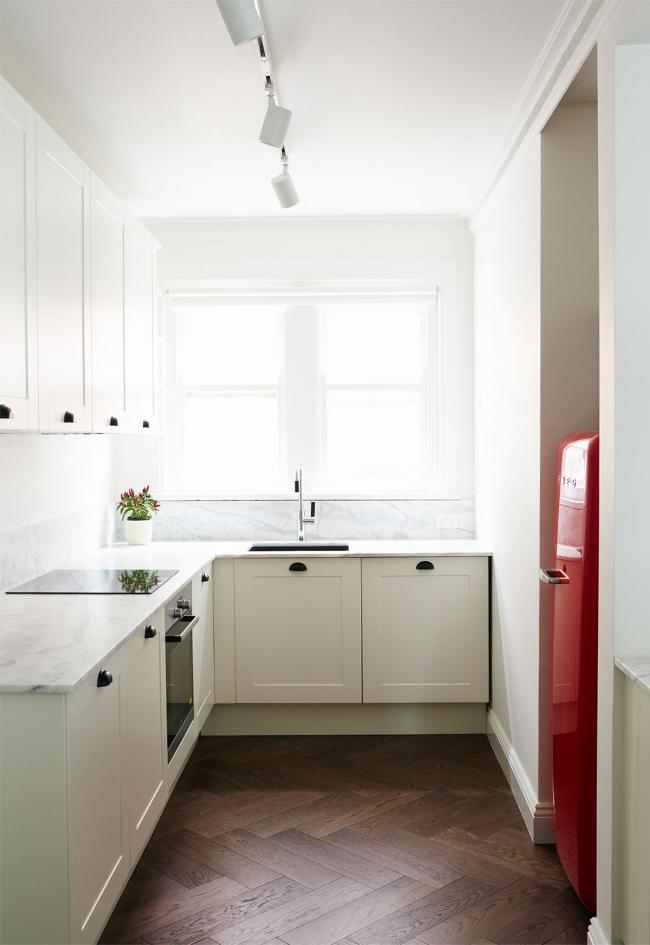 Смелое решение для небольшой светлой кухни - акцентировать все внимание на красном холодильнике