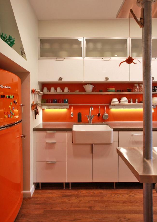 Оранжевый холодильник в тон кухонному фартуку с подсветкой на небольшой кухне