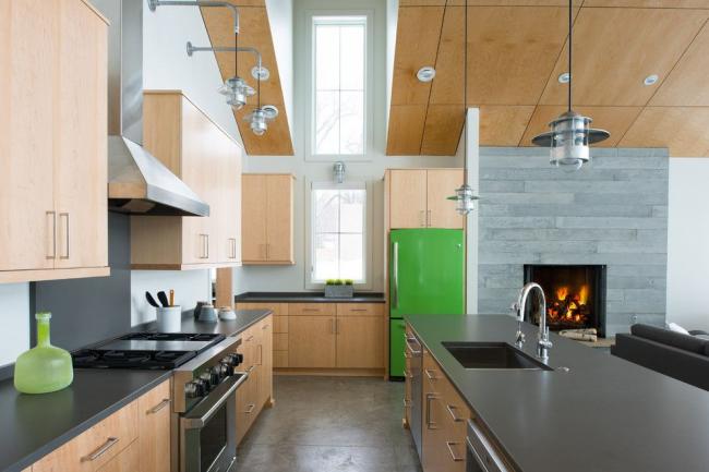Цветной холодильник сочного зеленого оттенка на просторной кухне с гарнитуром из светлого натурального дерева