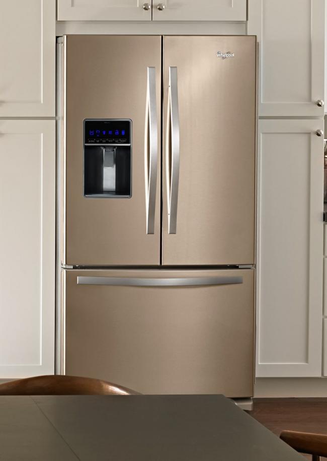 Большой встроенный холодильник металлического оттенка отлично сочетается со светлых кухонным гарнитуром