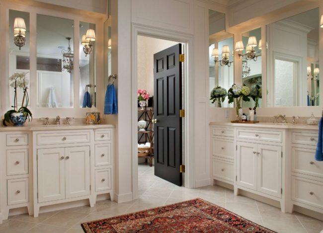 Темные деревянные филенчатые двери в светлом интерьере ванной комнаты