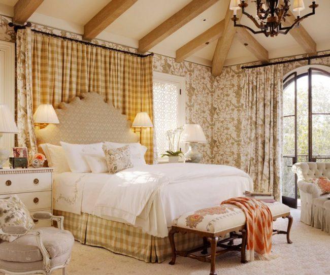 Французская кровать в загородном доме в стиле кантри - высокое изголовье криволинейной формы в пастельных тонах вписывается в общий интерьер помещения