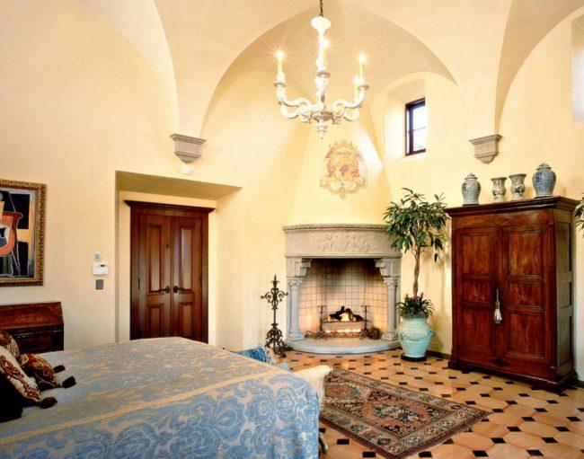 Нестандартный подход к оформлению спальни в готическом стиле: кованный подсвечник, рисунок герба над камином, а также светлая отделка стен и современные растения в комнате