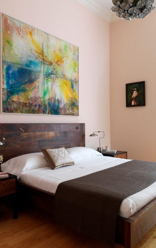 Картина с яркой абстракцией гармонично сочетается с деревянным изголовьем кровати и пастельным цветом стены