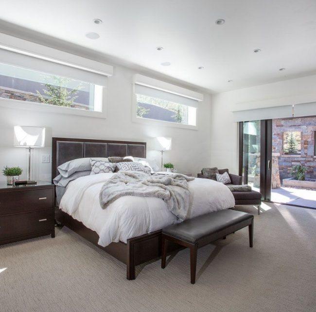 Размещение изголовья кровати вблизи небольших окон, разделенных с ней полоской стены - поможет вовсе решить проблему