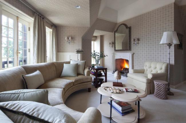 Домашняя уютная гостиная в бежевых тонах с камином, диваном округлой формы, журнальным столиком в виде облачка