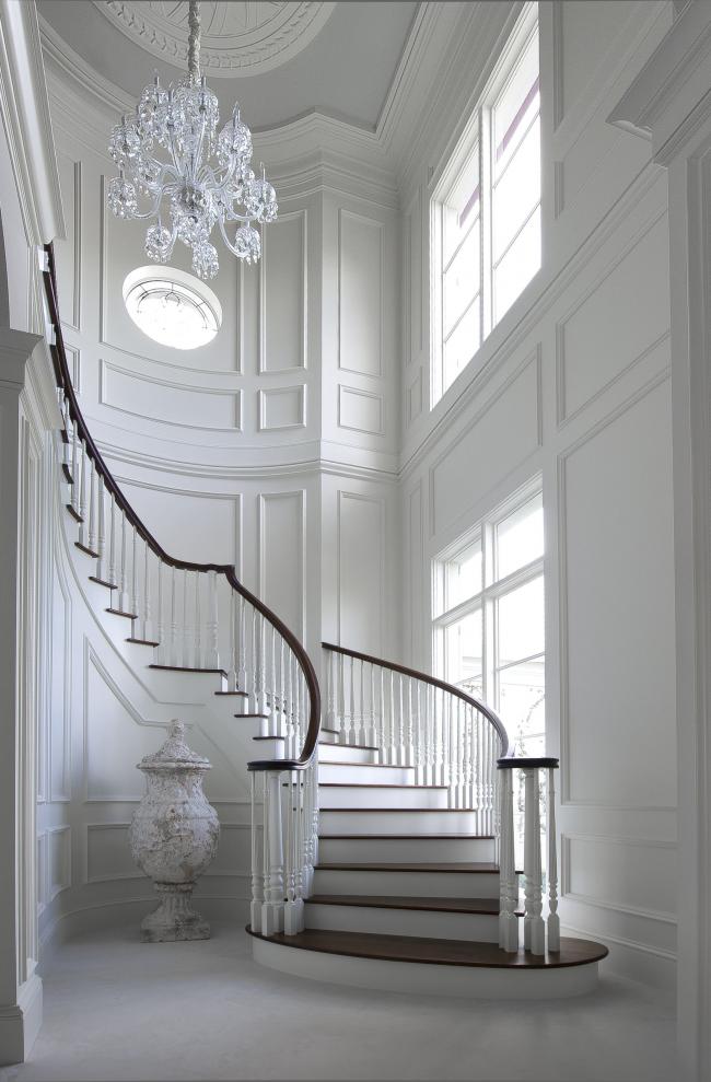 Холл загородного дома с обшивкой буазери под потолок выглядит дорого и изысканно. Выбирайте светлые тона и получите большое светлое помещение, наполненное воздухом и пространством