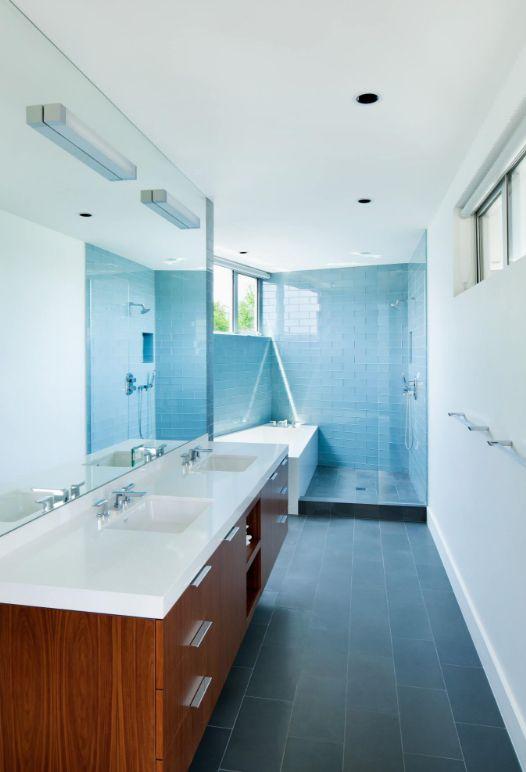 Голубая стеклянная плитка в узкой ванной добавит яркий цветовой акцент