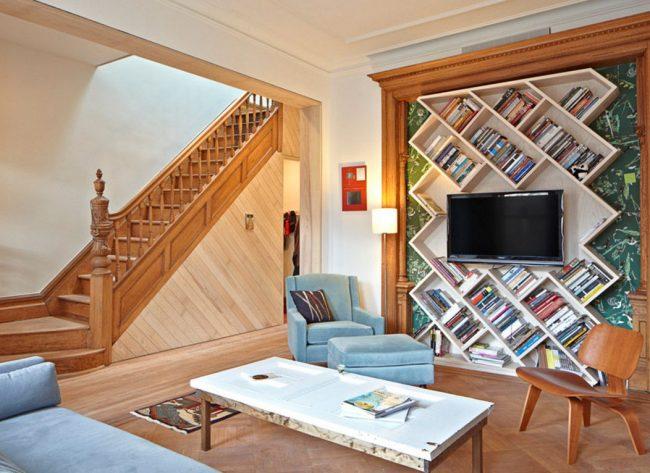 Дизайнерское решение для гостиной загородного дома: полка для телевизора размещена в разрез с диагональными полками для книг