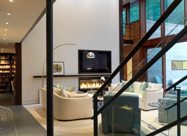 Разделение функциональных поверхностей в комнате: белая стена с длинной черной полкой для телевизора