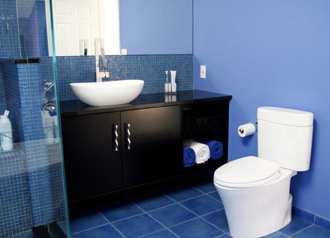 Синяя ванная комната: небольшая синяя ванная с темным мебельным гарнитуром и белоснежной сантехникой