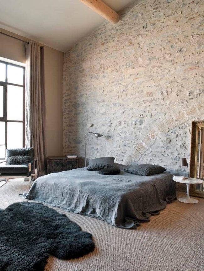 Спальня в стиле лофт с большим окном, кроватью с низким изголовьем и стильным журнальным столиком вместо тумбы