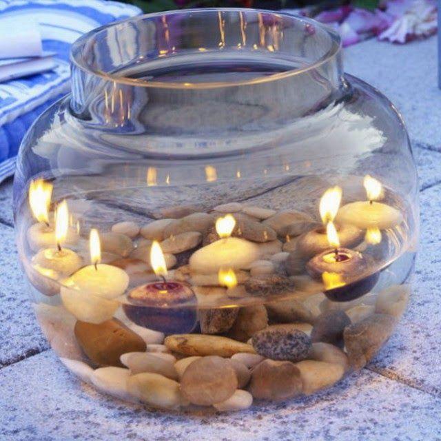 Круглые плавающие свечи в маленьком аквариуме с камнями