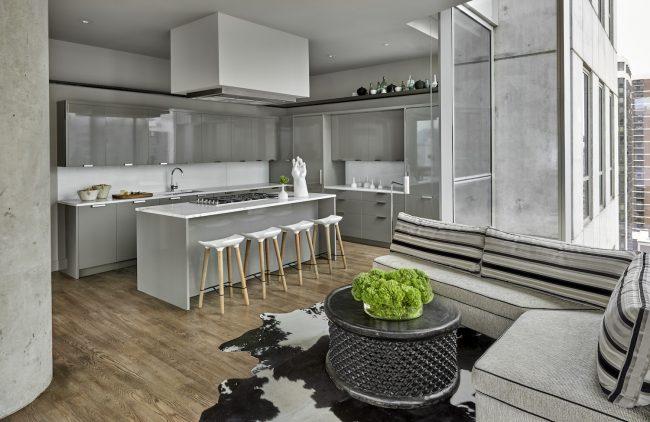 Кухня-студия в лофтовом духе с большой угловой тахтой у окна в зоне отдыха