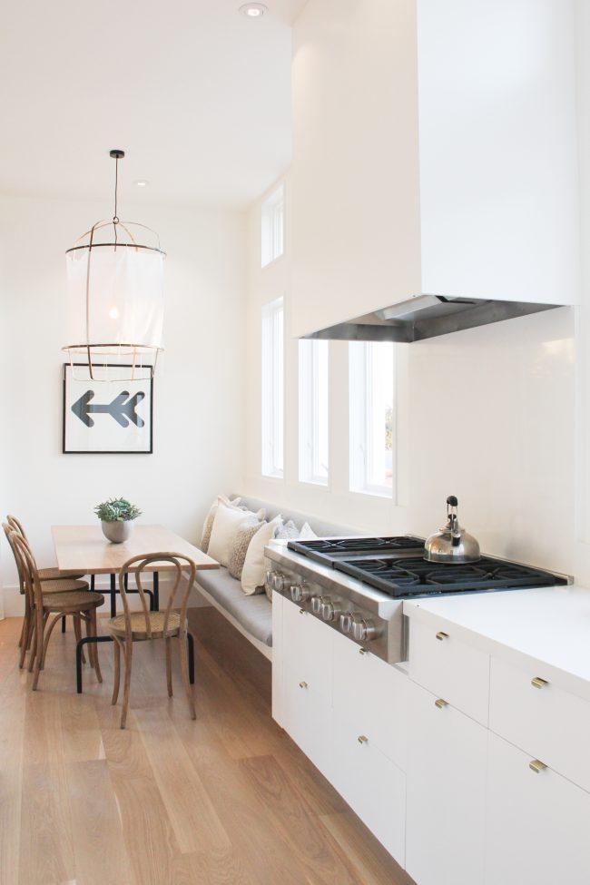 Очень уютная кухня в светлых тонах с яркими акцентами на темных элементах кухонного гарнитура и небольшой тахтой у окна