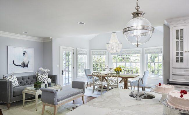 Просторная кухня-студия в частном доме с классической тахтой без спинки и небольшим диванчиком в зоне отдыха