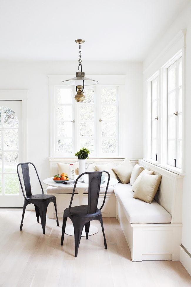 Классический вариант игры цветов на кухне с белоснежной тахтой и уютными подушками молочного оттенка
