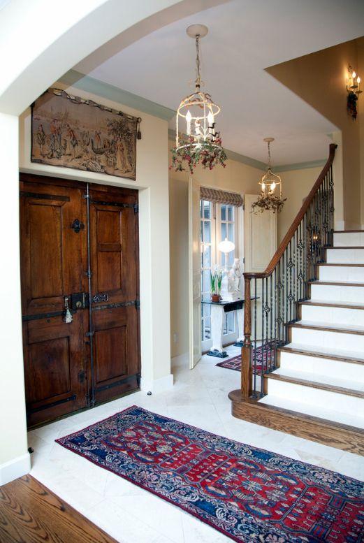 Светлый холл загородного домика в стиле прованс украшают темные деревянные двери
