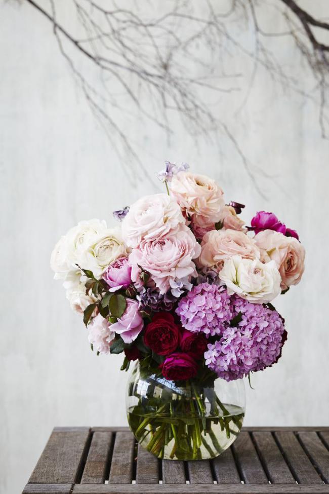 Милый и ухоженный букет и роз и сирени в прозрачной вазе